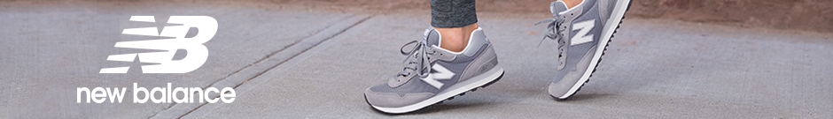 New Balance - a women wearing grey classic new balance running shoes on a sidewalk with a old brick wall in the background