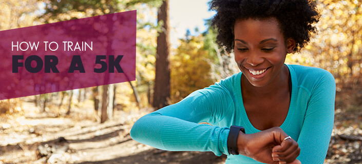 How To Train For A 5k - an afrian american women reading her watch in a forest on a dirt path in fall