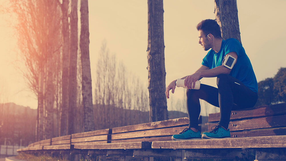 a man sitting on a wood bench on a tree lined path taking a break from running